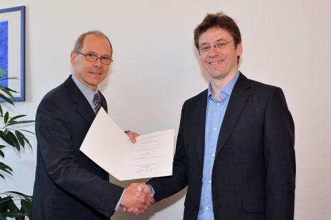 Thorsten Grosch (rechts) erhält die Ernennungsurkunde zum Universitätsprofessor von Dr. Georg Frischmann, dem hauptberuflichen Vizepräsidenten der TU Clausthal. Foto: Ernst