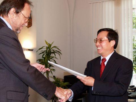 Privatdozent Dr. Michael Z. Hou (r.) erhält die Urkunde zum außerplanmäßigen Professor von Universitätspräsident Professor Thomas Hanschke.