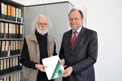 Professor Carsten Brauckmann nimmt die Verabschiedungsurkunde von Universitätspräsident Professor Thomas Hanschke entgegen. Foto: Ernst