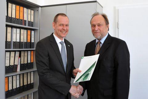 Dr. Dieter Dahmen (links) nimmt die Urkunde und die Glückwünsche von Universitätspräsident Professor Thomas Hanschke entgegen. Foto: Ernst