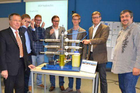 Professor Joachim Oppelt (links) und Dr. Catalin Teodoriu (rechts) rahmen die fünf siegreichen Studenten ein, die eine Kombination von Bohrlochsicherungsventilen im Modell erstellten.