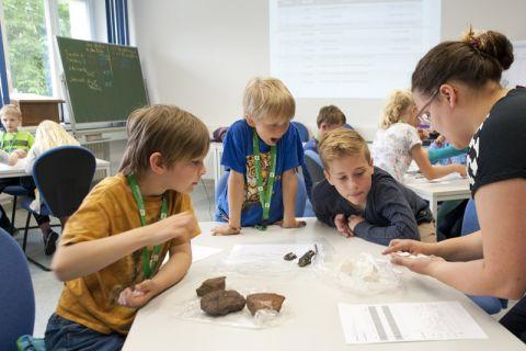 Angela Binder (rechts) erklärt Emil, Mio und Laurenz (von links), was beim Beschreiben der Steine zu tun ist. Foto: Ernst