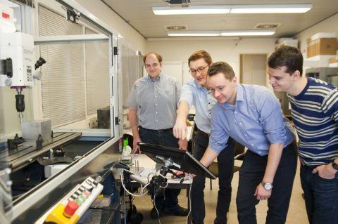 Diplom-Ingenieur Joachim Langenbach (links) beobachtet, wie die Maschinenbau-Studenten Mirco Fuhrmann, Julian Dreblow und Timo Roth eine Fräse einrichten. Foto: Ernst
