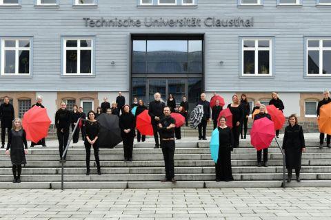 Kammerchor der TU Clausthal vor dem Hauptgebäude der Universität. Foto: Ezra Wolfhart Kurth