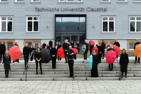 Der Kammerchor an der TU Clausthal vor dem Hauptgebäude der Universität. Foto: Ezra Wolfhart Kurth