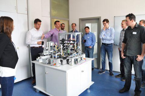 Professor Andreas Rausch (3. von links), Initiator des neuen IT-Netzwerkes, stellt einigen Teilnehmern ein Projekt aus dem Bereich Industrie 4.0 vor. Foto: Ernst