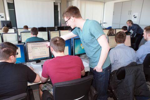 Masterstudent Marius Reppe, zugleich Tutor des Seminars, gibt Erläuterungen, damit die Studierenden lernen, Planungsprozesse für den Karosseriebau am Computer zu simulieren. Foto: Ernst