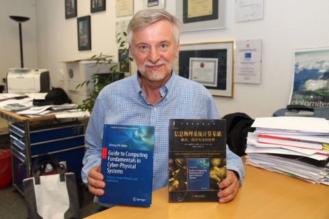 """Der Clausthaler Professor Dietmar Möller zeigt sein Buch """"Guide to Computing Fundamentals in Cyber-Physical Systems"""" und daneben die neue, noch eingeschweißte Fassung auf Chinesisch. Foto: Hoffmann"""