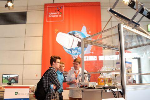 """Dr. Andreas Czymai (TU) erläutert Schülern das Projekt """"Sonnenlicht tanken"""": Über ein Solarmodul wird eine innovative Batterie mit Energie aufgeladen, die wiederum als  elektrischer Strom zum """"Betanken"""" von Modellautos genutzt wird. Foto: Ernst"""
