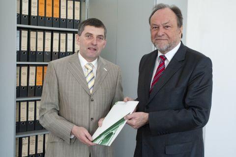 Dr. Roland Strauß (links) nimmt die Bestellungsurkunde zum Honorarprofessor von Universitätspräsident Professor Thomas Hanschke entgegen. Foto: Bruchmann