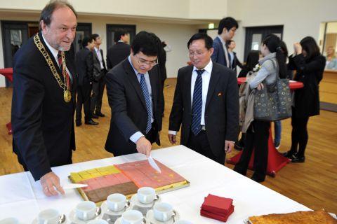 Beim Anschneiden einer deutsch-chinesischen Torte auf der Festveranstaltung (von links):  Universitätspräsident Professor Thomas Hanschke, Dr. Zhao Qinghua von der chinesischen Botschaft in Berlin und Professor Michael Z. Hou. Foto: Ernst