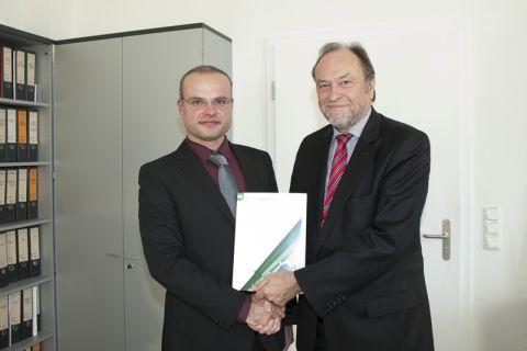 Dr. Thomas Niemand (links) erhält von Universitätspräsident Professor Thomas Hanschke die Ernennungsurkunde. Foto: Ernst