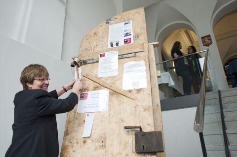 """Pastorin Andrea Siuts schlägt eine These an eine der beiden """"Reformationstüren"""", die im historischen Eingangsbereich der TU Clausthal aufgestellt sind. Foto: Ernst"""