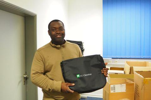 Maschinenbau-Student Marcel Dossou packt die TUC-Start-Taschen, die an alle neuen Studierenden verteilt werden. Foto: Hoffmann