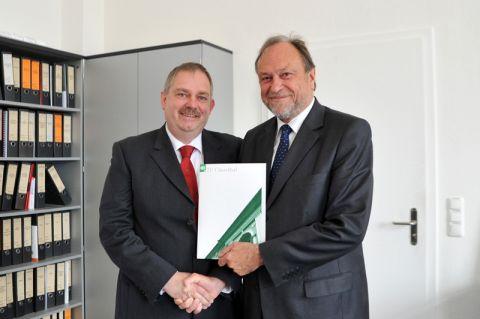 Privatdozent Dr. Martin Tegtmeier (links) erhält von Universitätspräsident Professor Thomas Hanschke die Urkunde. Foto: Ernst