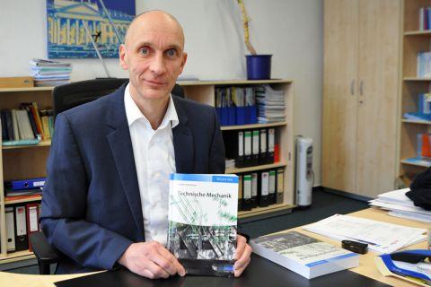 """Professor Stefan Hartmann präsentiert den mehr als 600 Seiten starken Band """"Technische Mechanik"""", der zu Jahresbeginn herausgekommen ist. Foto: Ernst"""