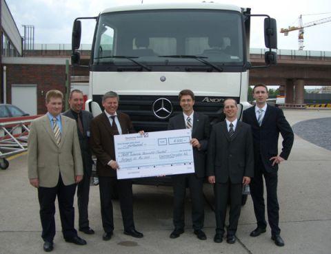 Prof. Dr.-Ing. Uwe Bracht erhält von Dr.-Ing. Henning Oeltjenbruns nach erfolgreicher Probefahrt mit dem neuen Mercedes-Benz Lkw Axor auf der Teststrecke im Werk Untertürkheim einen Spendenscheck von DaimlerChrysler für das IMAB.