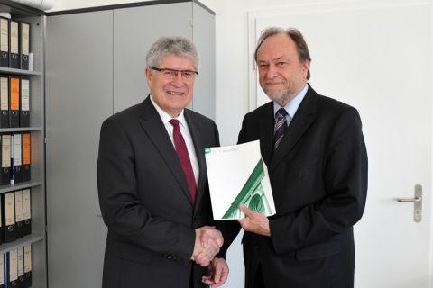 Dr. Dieter Meiners (links) erhält die Ernennungsurkunde von Universitätspräsident Professor Thomas Hanschke. Foto: Ernst