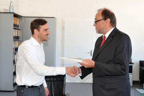 Dr. Matthias Greiff (links) erhält von Universitätspräsident Professor Thomas Hanschke die Ernennungsurkunde zum Juniorprofessor. Foto: Melanie Bruchmann