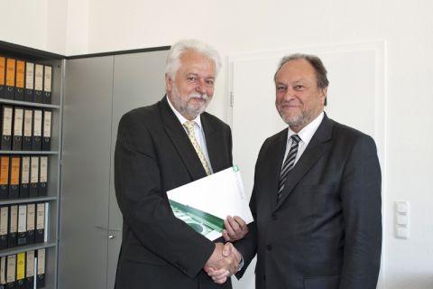 Professor Norbert Müller (links) erhält von Universitätspräsident Professor Thomas Hanschke die Verabschiedungsurkunde.